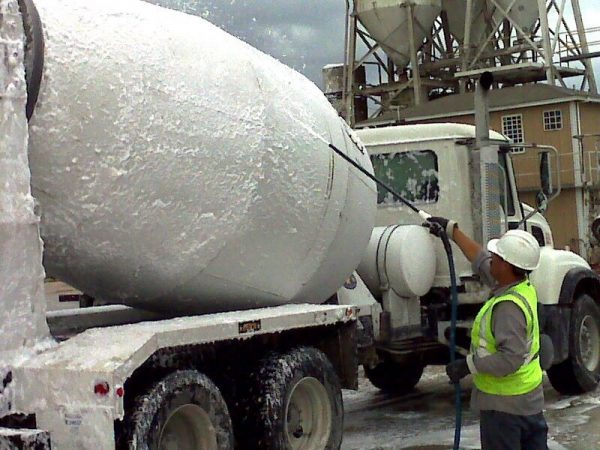 Man cleaning a truck wearing protective wear