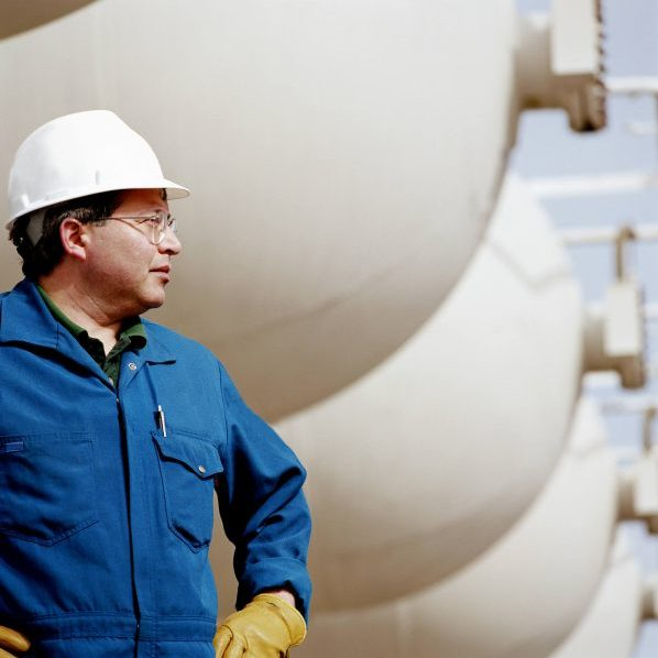 Engineer in front of chemical tanks